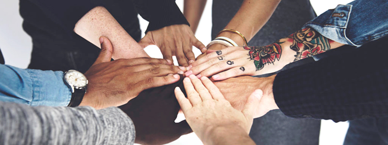 diverse hands together in a circle