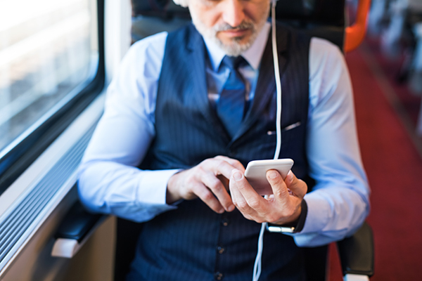 photo of man on a train listening to a podcast on his phone