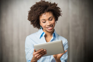 photo of a woman listening to a webinar on a tablet