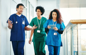 Group of medical professionals with digital tablet discussing along hospital corridor.