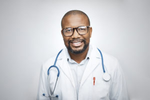 Portrait of medical professional wearing eyeglasses on white background. Confident doctor is smiling. He is in lab coat.